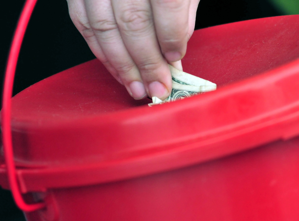 A donor stuffs money into a Salvation Army red kettle in December 2014.