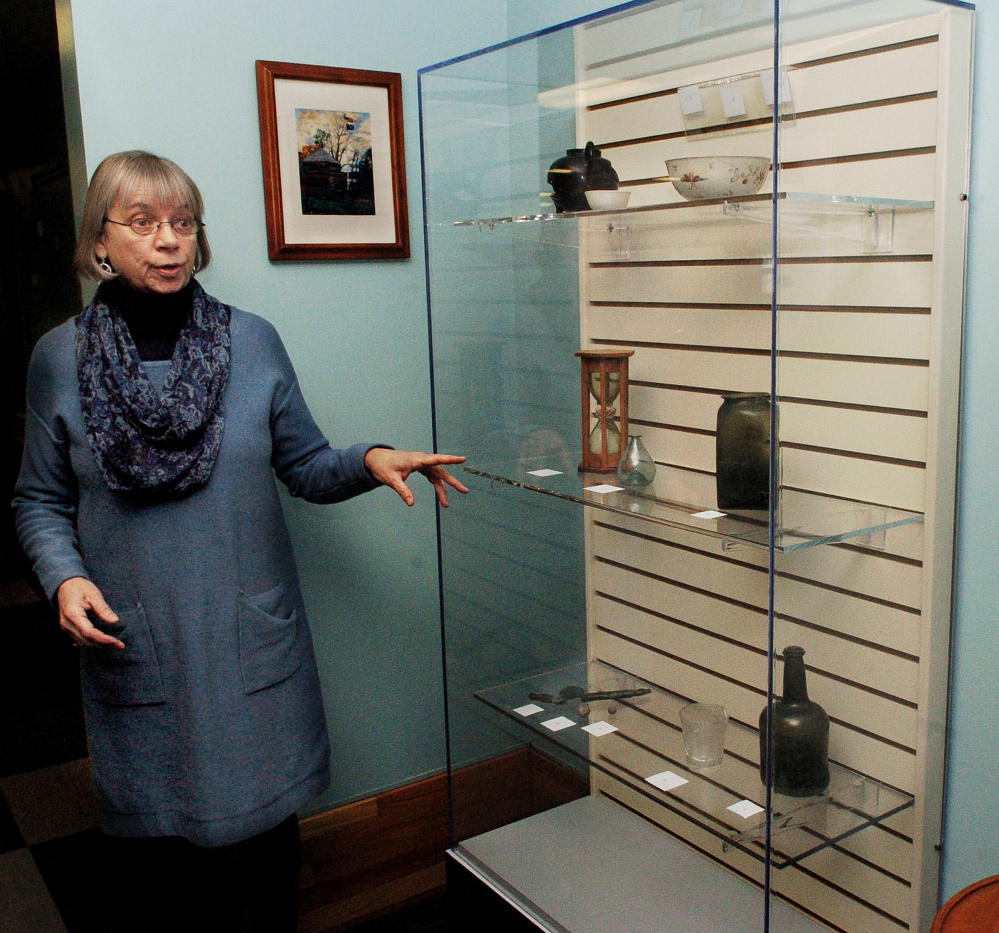 Winslow Public Library Director Pamela Bonney speaks about the library's new archival exhibit case, which contains items from the Fort Halifax Archaeological Collection, on Wednesday. The case allows old and sensitive items to be stored in a protective environment.