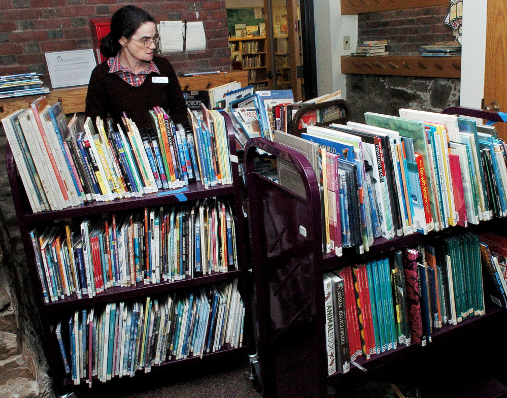 Waterville Public Library Children's Librarian Kathleen Kenny organizes salvaged books Thursday at the library. She and volunteers were putting the library back in order after a burst water pipe caused serious damage last weekend.
