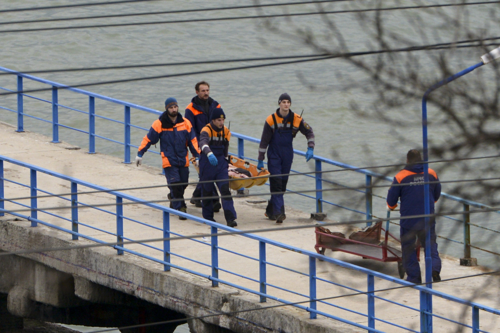 Russian rescue workers carry a body from the wreckage of the crashed plane, at a pier just outside Sochi, Russia, on Sunday.