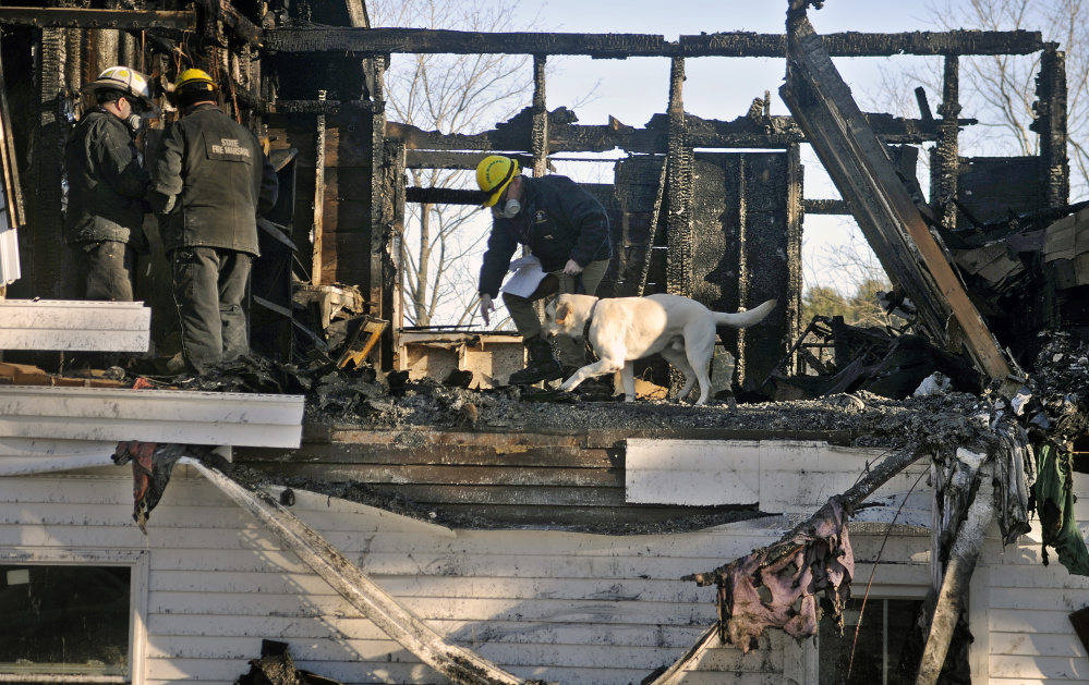 Investigators Chris Stanford, left, and Ed Archer of the Office of Maine State Fire Marshal observe their colleague Jeremy Damren handle his accelerant sniffing dog, Harry, while searching the burned remnants of a second floor apartment in a building in Richmond Sunday.