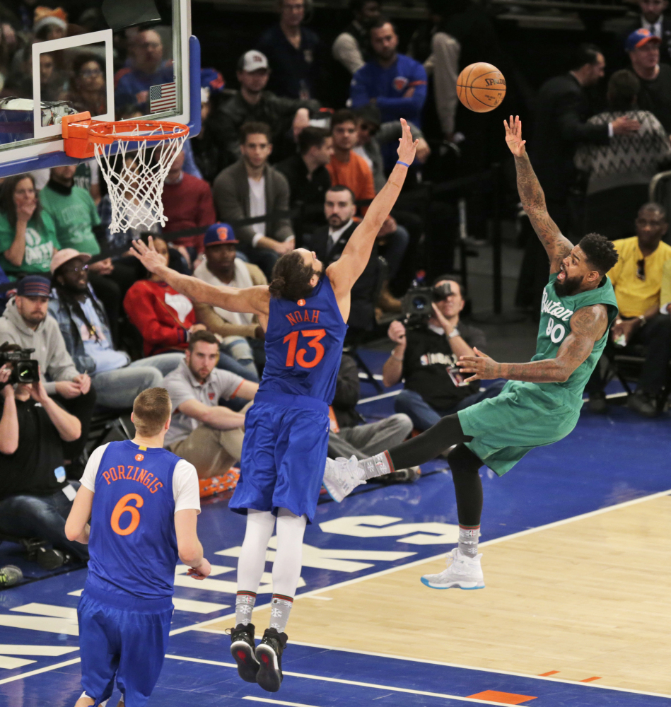 Boston's Amir Johnson, right, puts up a shot over New York Knicks' Joakim Noah (13) during the second half Sunday in New York.