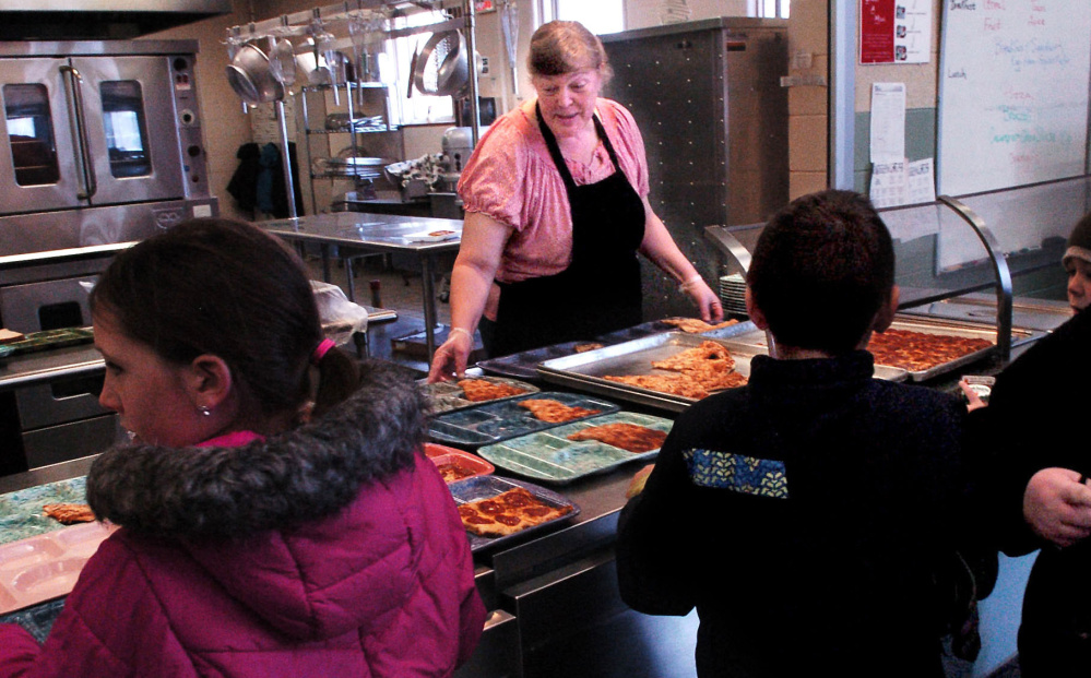 Winslow Elementary School food service employee Vicki Perry sets out lunches for students on Wednesday. Starting Jan. 3, the school will pilot a food-waste recycling program that involves the Agri-Cycle Energy processing plant in Exeter.