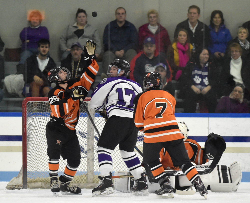 Winslow's Tyler Martin, left, tries to swat the puck out of the air as Waterville's Cooper Hart (17) looks for the rebound Tuesday at Colby College in Waterville.