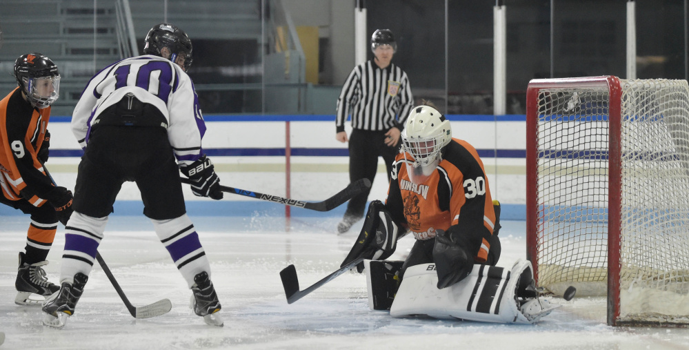 Winslow goalie Ben Grenier (30) can't make the save as Waterville's Matt Jolicoeur (10) looks for the rebound Tuesday at Colby College in Waterville.