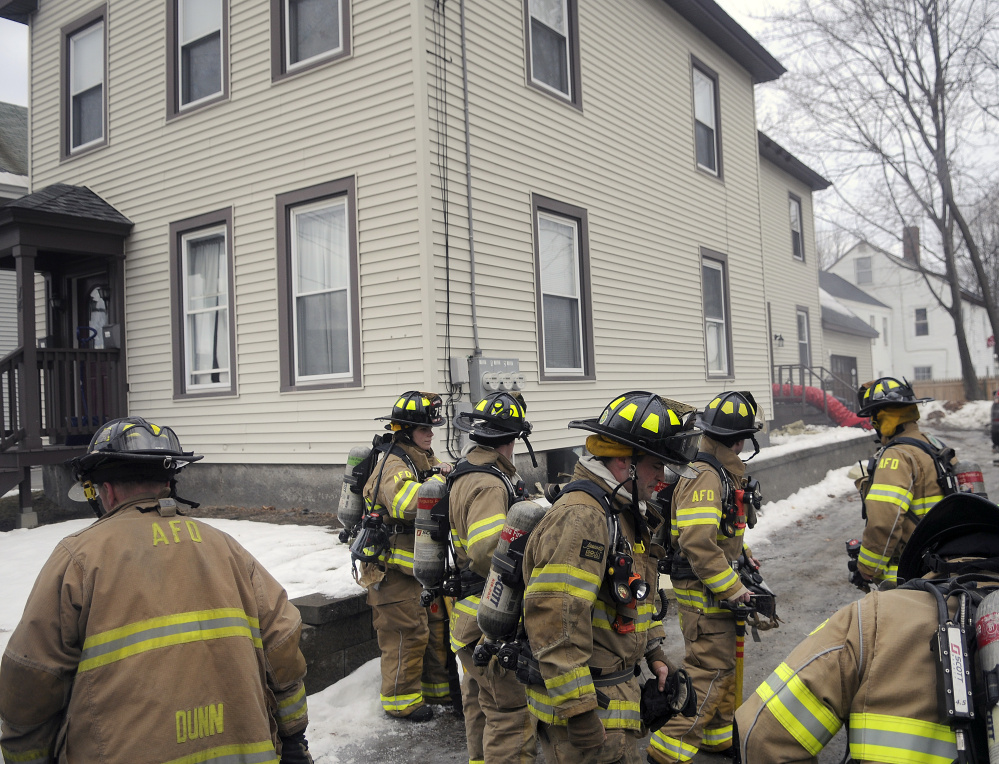 Augusta firefighters gather on Wednesday outside a building on Winthrop Court in Augusta after the building's boiler overheated, sending smoke into the two-unit house.