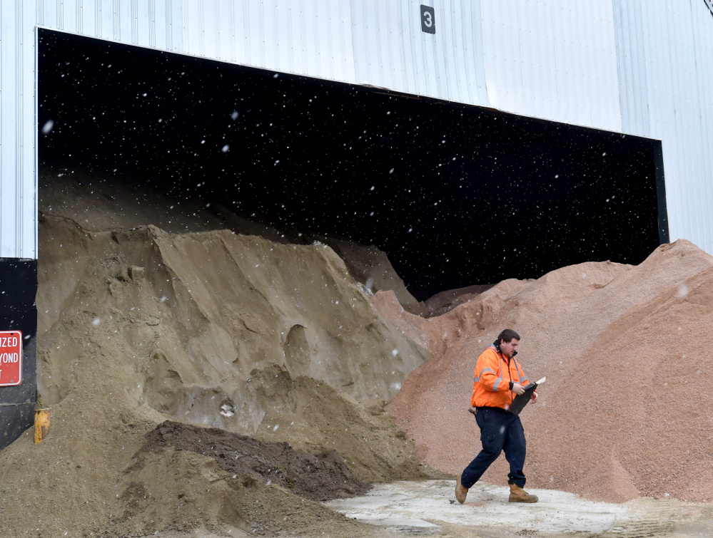 Bobby Bellows removes a piece of trash from the sand and salt piles at the Waterville Public Works yard in Waterville on Thursday, as a Nor'easter moved into the region.
