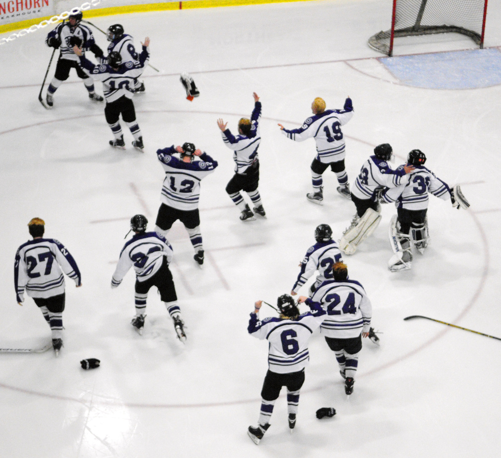 The Waterville hockey team celebrates after it won the Class B state championship last season at Androscoggin Bank Colisse in Lewiston.