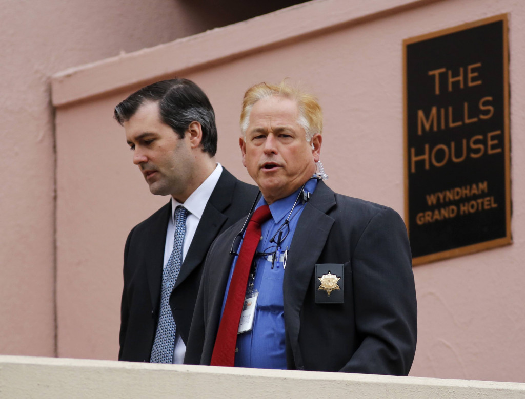 Michael Slager, left, walks from The Mills House Hotel to the Charleston County Courthouse under the protection from the Charleston County Sheriff's Department during a break in the jury deliberations for his trial on Monday.
