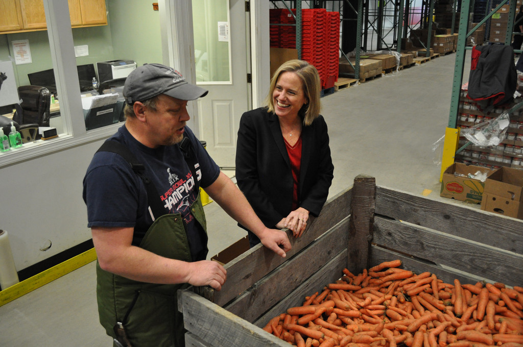 Good Shepherd Food Bank of Maine President Kristen Miale and warehouse staffer Rusty Cooper look over produce at the nonprofit's distribution center in Auburn. (Photo by Ryan Fecteau.)