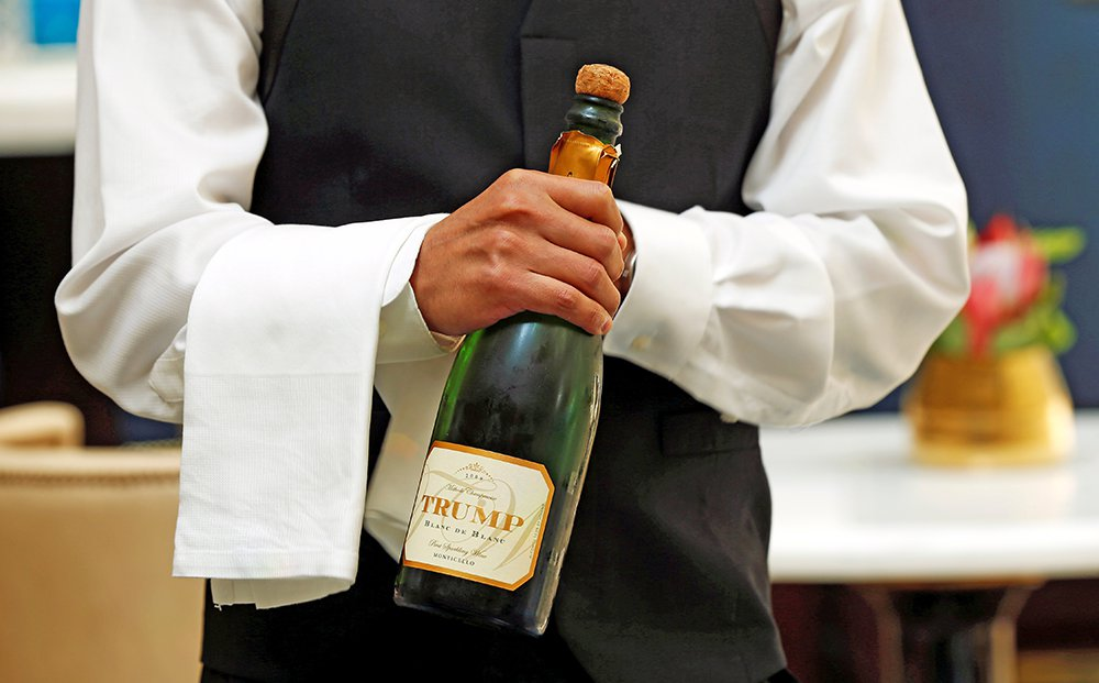 """A waiter opens a bottle of Trump champagne for the first guests to arrive at the Trump International Hotel on its """"soft opening"""" day in Washington on Sept. 12, 2016. <em>Reuters/Kevin Lamarque</em>"""