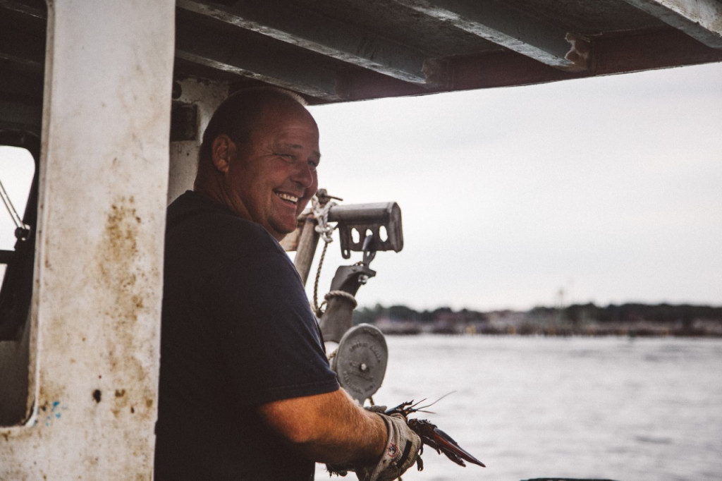 """Jim Buxton, shown on his lobster boat in Casco Bay, appears in a new online documentary series """"Wharfside: Stories From Portland Harbor's Working Waterfront."""" Buxton, 49, is a lobsterman and shellfish diver who has been tying up at Merrill's Wharf in Portland for more than 20 years, and he hopes the city continues to support a working waterfront. Photo by Jenny Rebecca Nelson/ Courtesy of Galen Koch"""