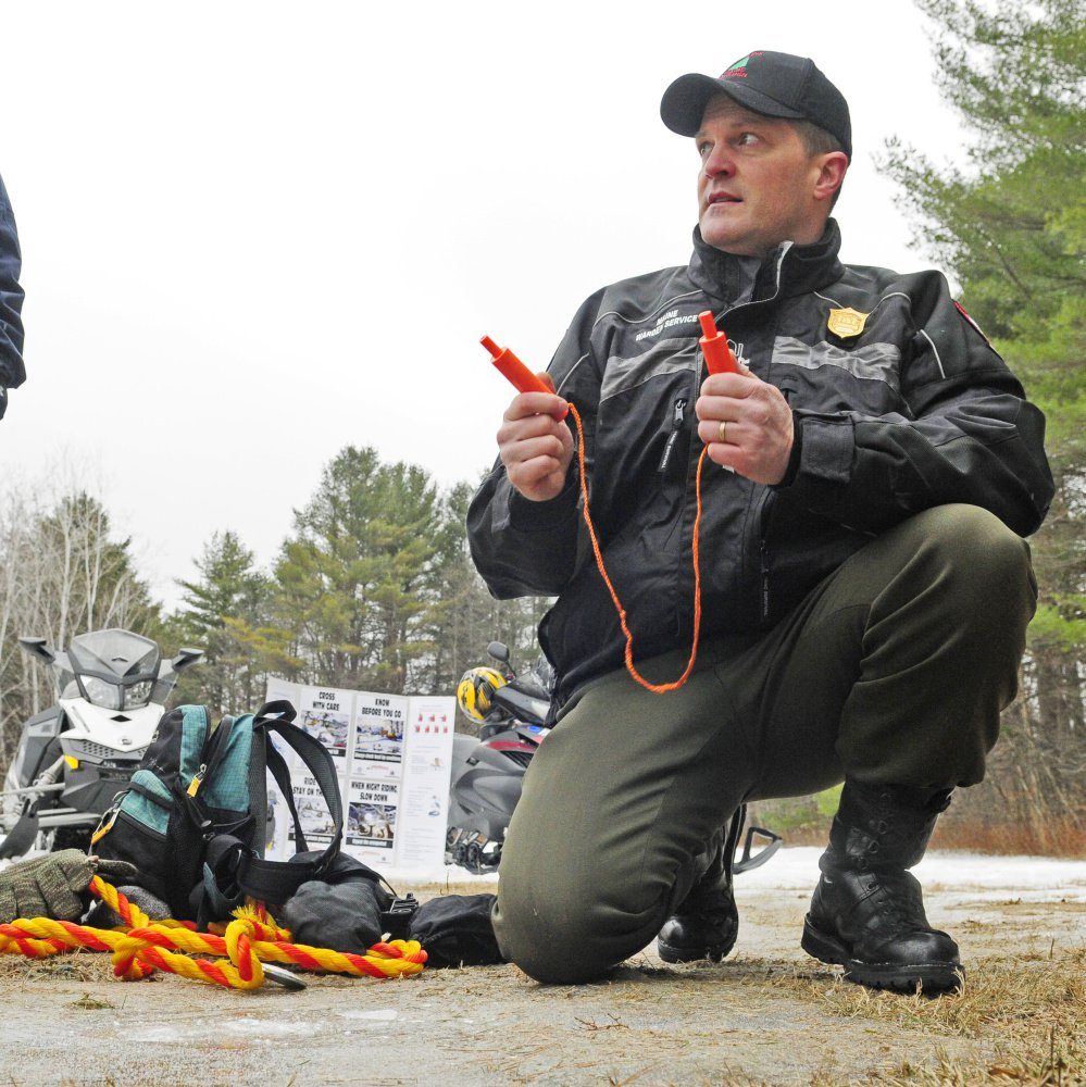 Maine Warden Service Cpl. John MacDonald holds up ice picks while talking during Thursday's news conference about why snowmobilers should carry packs with safety gear, food and dry clothes.