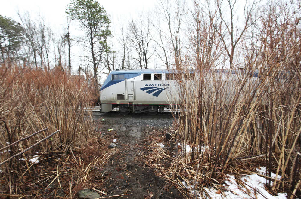 A Downeaster train travels northbound parallel to First Street, near where Carson Filiault accidentally backed over an embankment from his apartment, jumping out of his truck just before it was crushed by a passing Downeaster train.