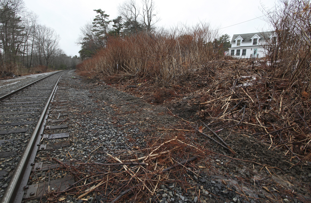 Carson Filiault accidentally backed over an embankment near his apartment, at right, on Wednesday and ended up on the train tracks just as a Downeaster was approaching.