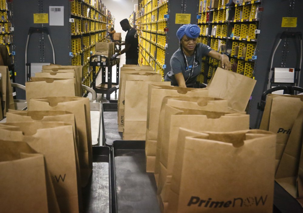 Amazon PrimeNow workers fill orders from customers at a distribution center in New York. Amazon is planning to hire 100,000 workers in the U.S. over the next 18 months, and many of them will be at new fulfillment centers being built in states such as California, Florida and Texas. The company is also adding to its delivery capabilities.