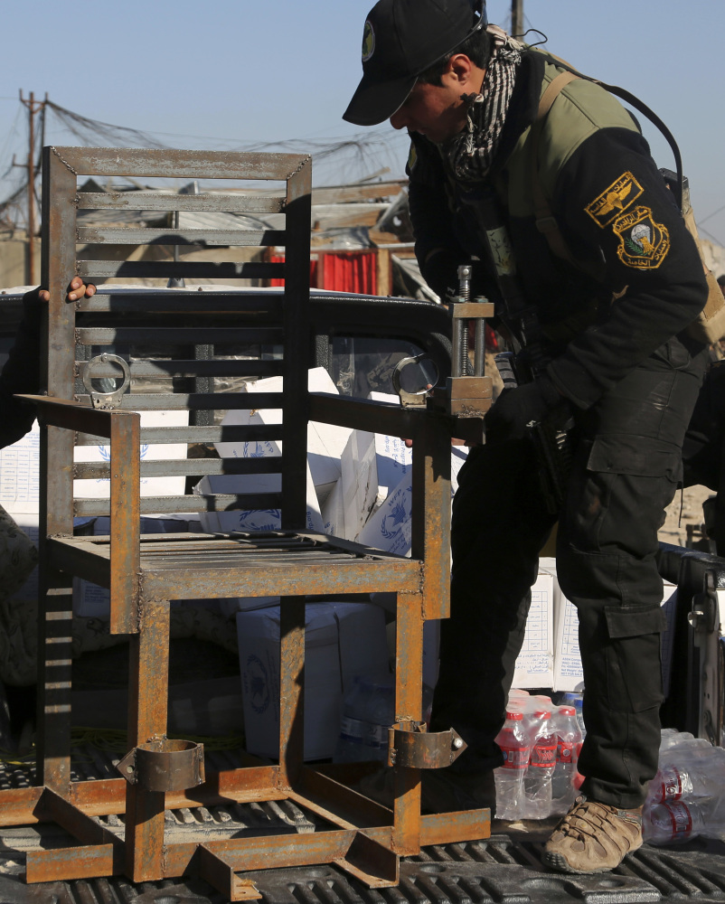 Iraqi special forces display a chair they say militants used to torture people, found in a detention facility.