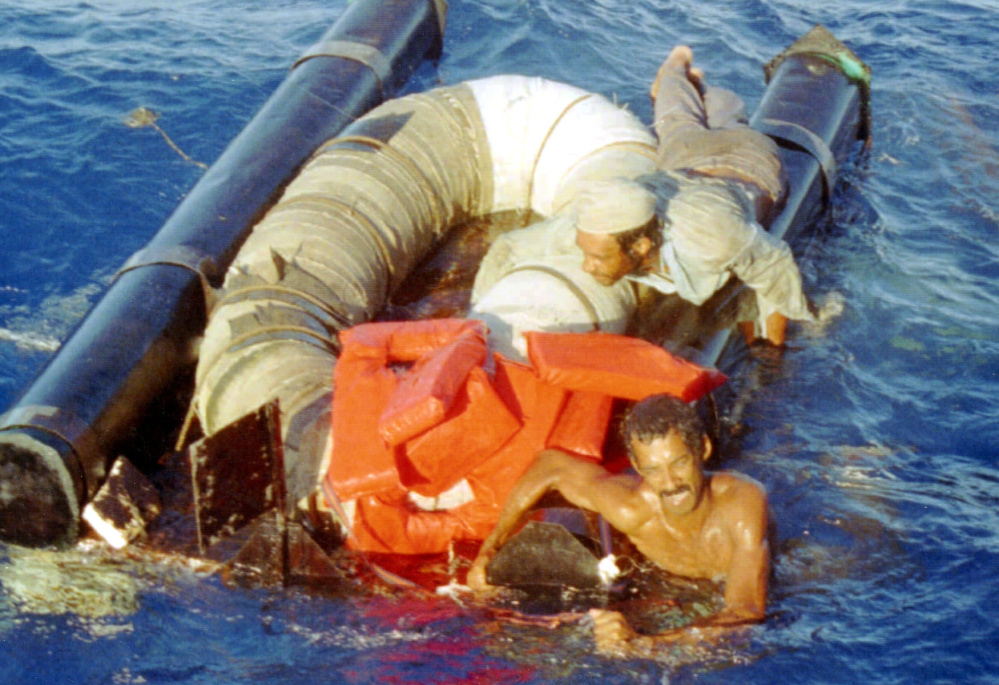 Refugees cling to their overturned raft in 1994 as the Coast Guard cutter Chandeleur moves in to pick them up north of Cuba. Cubans arriving by water have been favored by immigration policy since 1995.