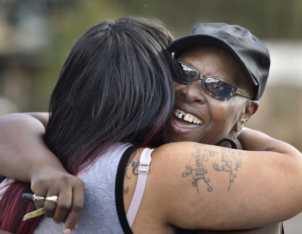 Velma Aiken, the paternal grandmother of Kamiyah Mobley, who was kidnapped as an infant 18 years ago, gets a congratulatory hug from a family member after Mobley was found safe, Friday in Jacksonville, Fla.