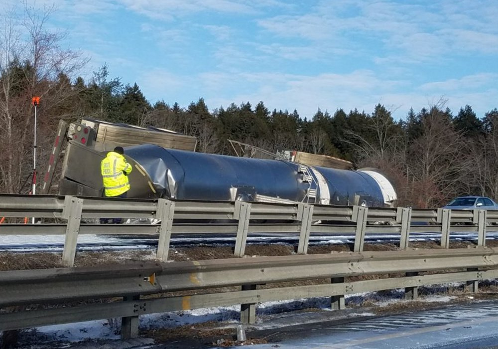 A tanker truck carrying milk lies on its side after a fatal crash on I-295 in Freeport on Saturday.