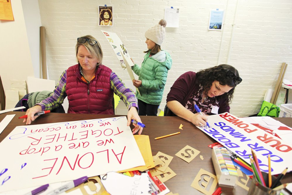 Kristen Farnham, left, and her daughter Audrey, 9, work alongside Beth Penrose as people prepare signs to carry at a protest of the inauguration of President-elect Donald Trump.