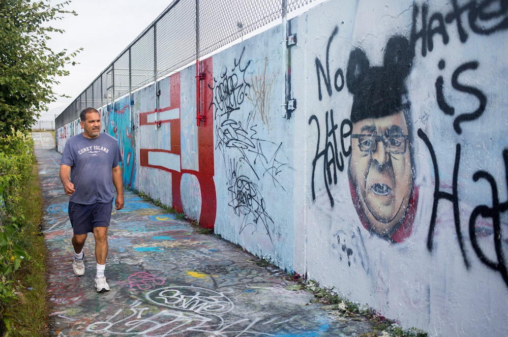 Karl Miller of Portland walks past the image of Gov. Paul LePage on the graffiti wall on Portland's Eastern Promenade last year. The Portland Water District held a public hearing Wednesday night on whether graffiti artists should continue to use the wall.