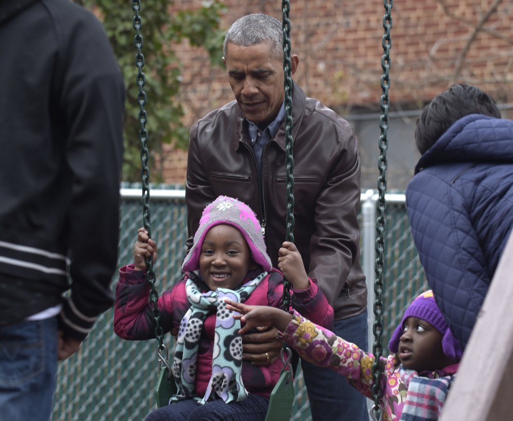 "President Obama pushes kids on the swings as they visit ""Malia and Sasha's Castle"" that the Obamas donated to the Jobs Have Priority Naylor Road Family Shelter."
