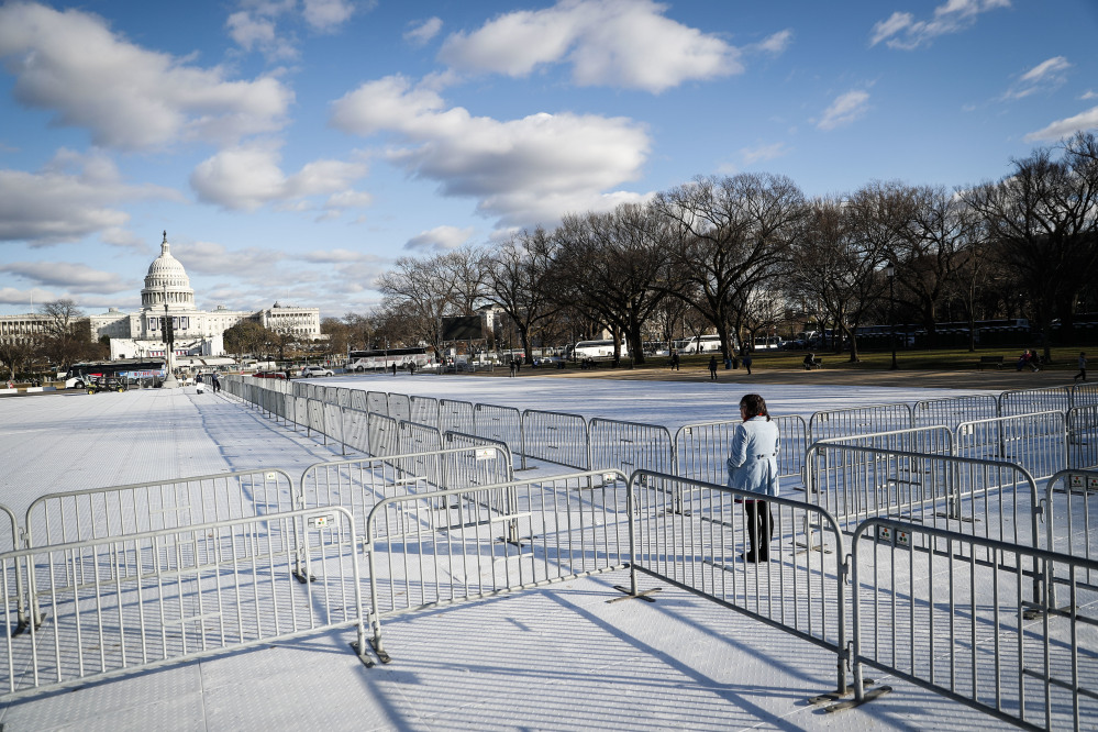 A pedestrian stand at the intersection of barricades dividing areas of standing room on the National Mall in Washington, Wednesday, Jan. 18, 2017, as preparations continue for Friday's presidential inauguration. (AP Photo/John Minchillo)