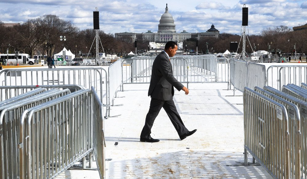 A pedestrian walks through the National Mall in Washington, Wednesday as the Capitol readies for Friday's crowds.