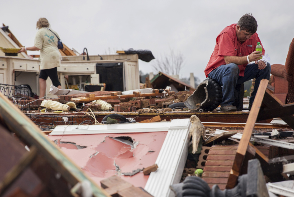 Jeff Bullard sits in what used to be the foyer of his home as his daughter Jenny Bullard looks through debris after their house was severely damaged by a tornado early Sunday in Adel, Ga.