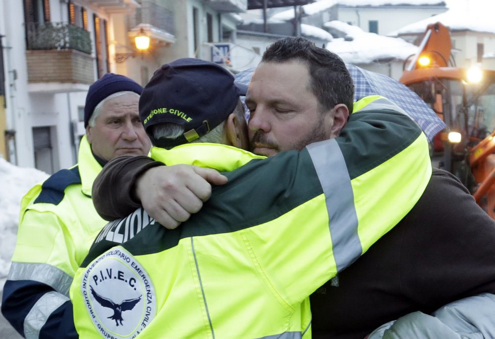 Massimiliano Giancaterino, right, the brother of a victim of the avalanche which buried the Hotel Rigopiano, is hugged by an Italian Civil Protection volunteer Sunday.