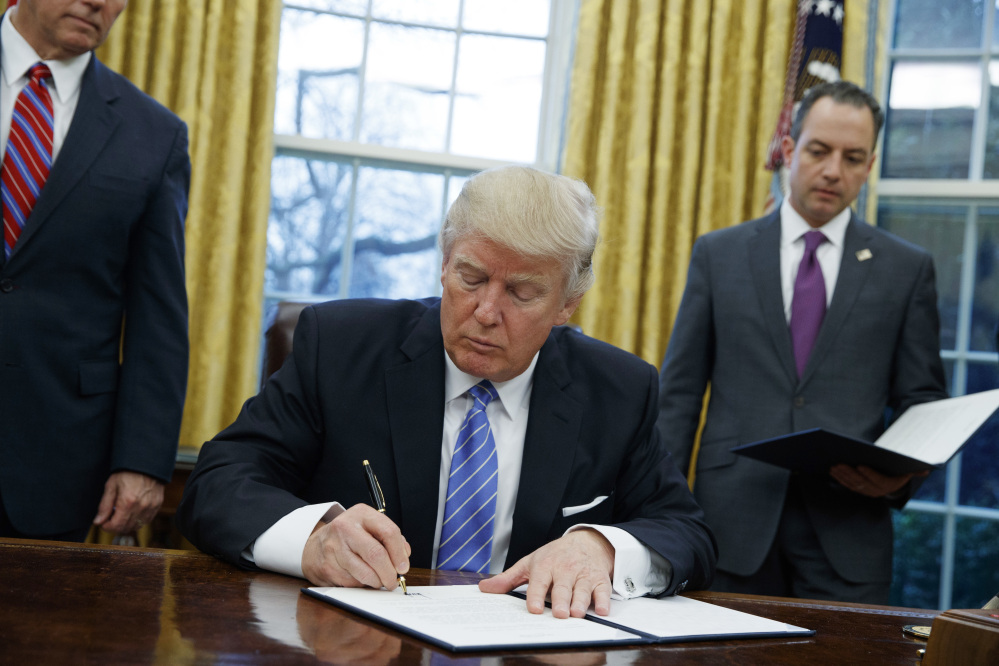 President Donald Trump signs an executive order to withdraw the U.S. from the 12-nation Trans-Pacific Partnership trade pact agreed to under the Obama administration in the Oval Office of the White House in Washington on Monday. Trump's policy changes could inadvertently give China room to assert itself as a regional leader and worsen strains over the South China Sea and Taiwan.