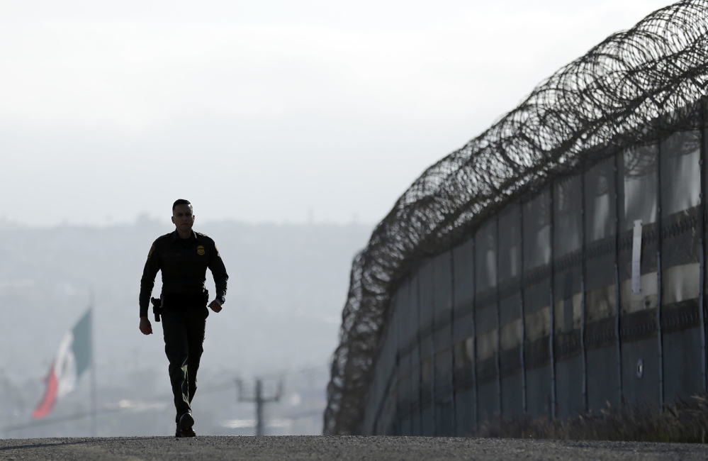A Border Patrol agent Eduardo Olmos walks near the secondary fence separating Tijuana, Mexico, background, and San Diego in San Diego last June. The Border Patrol chief has left his job.