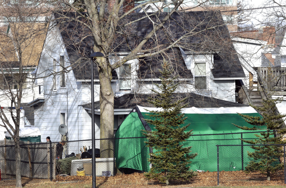 Officials search for clues in a missing person's case behind at tent last week  in the back of a house in Manchester, N.H. The case is linked to four bodies found between 1985 and 2000.