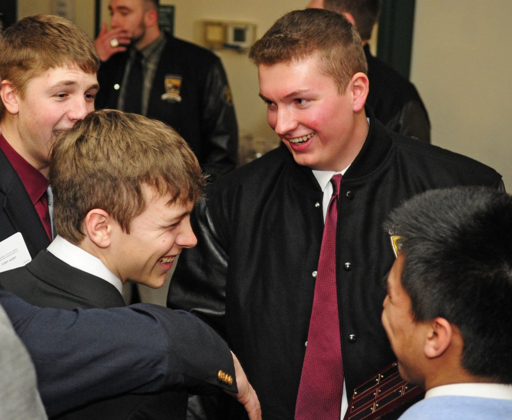 Thornton Academy's Nicholas Bartholomew, top right, is congratulated by teammates after winning the 2016 the Frank Gazianao Offensive Lineman of the Year on Saturday at the Augusta Civic Center. (Staff photo by Joe Phelan/Staff Photographer)