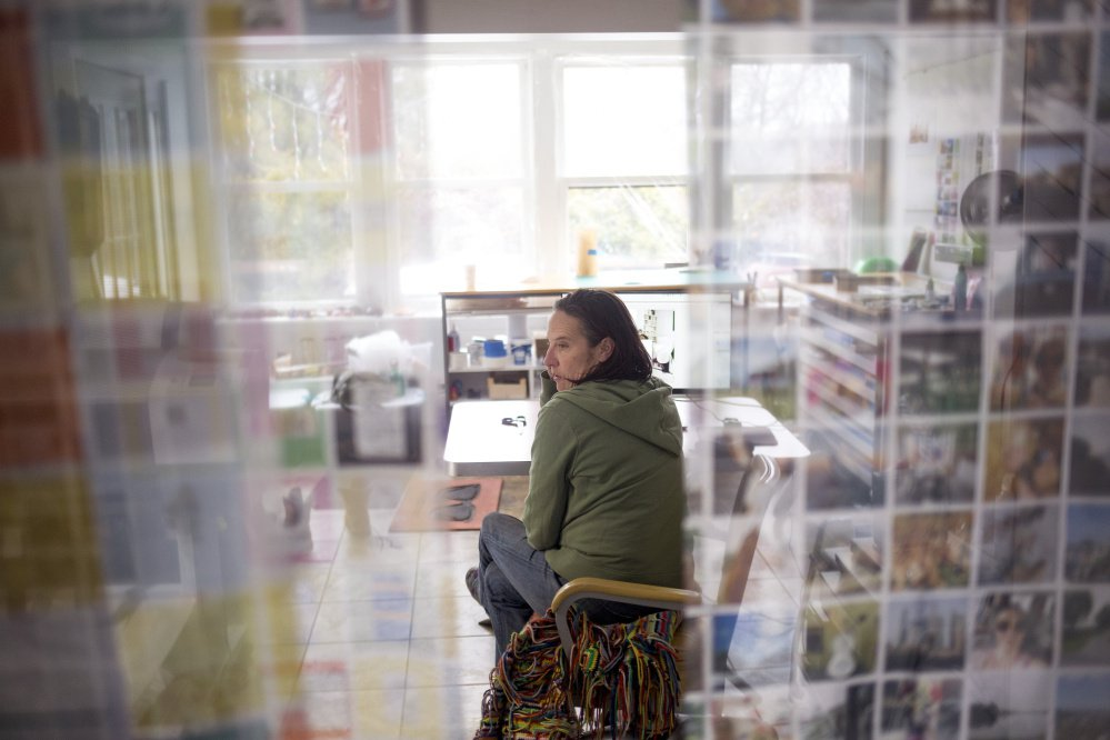 """Tanja Hollander is surrounded by prints of her photos in her studio at her home in Auburn as she prepares for the opening of her exhibition """"Are You Really My Friend"""" on Feb. 18 at Mass MoCA in North Adams, Mass. Hollander spent five years photographing her Facebook friends around the world."""