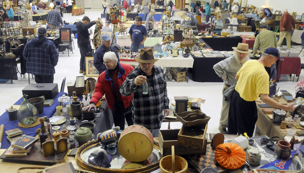 People examine items for sale during the antique show Sunday in Augusta.