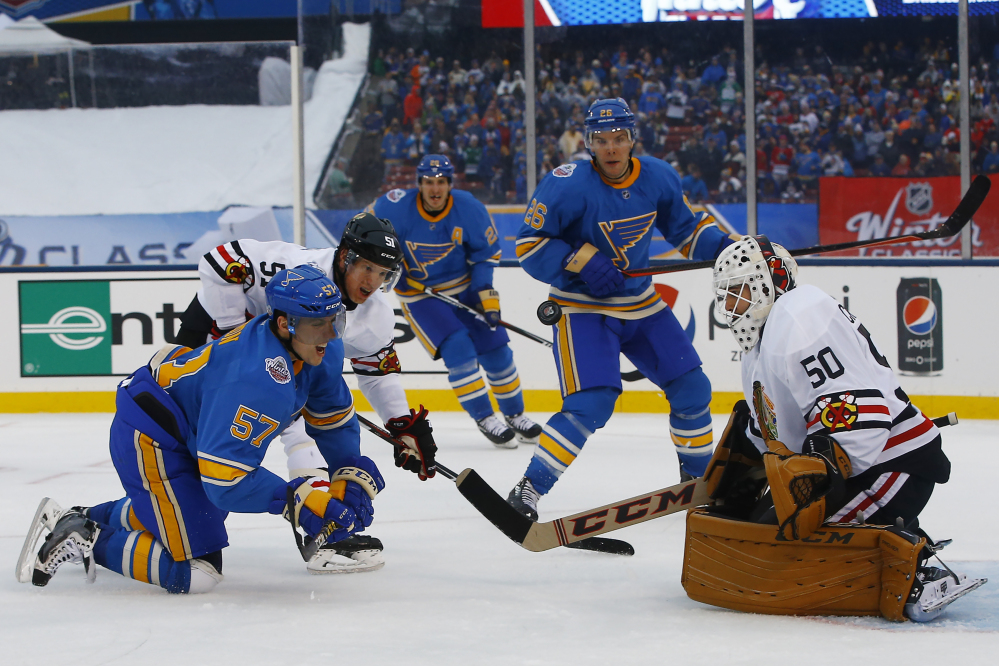 St. Louis Blues' David Perron, left front, is checked to the ice by Chicago Blackhawks' Brian Campbell, second from left, after taking a shot against Blackhawks goalie Corey Crawford, right, during the second period of the NHL Winter Classic on Monday at Busch Stadium in St. Louis.