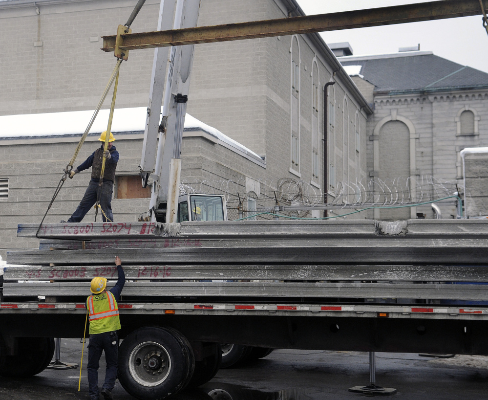 Workers lift material inside the Kennebec County Correctional Facility Tuesday as renovations and an expansion begins.