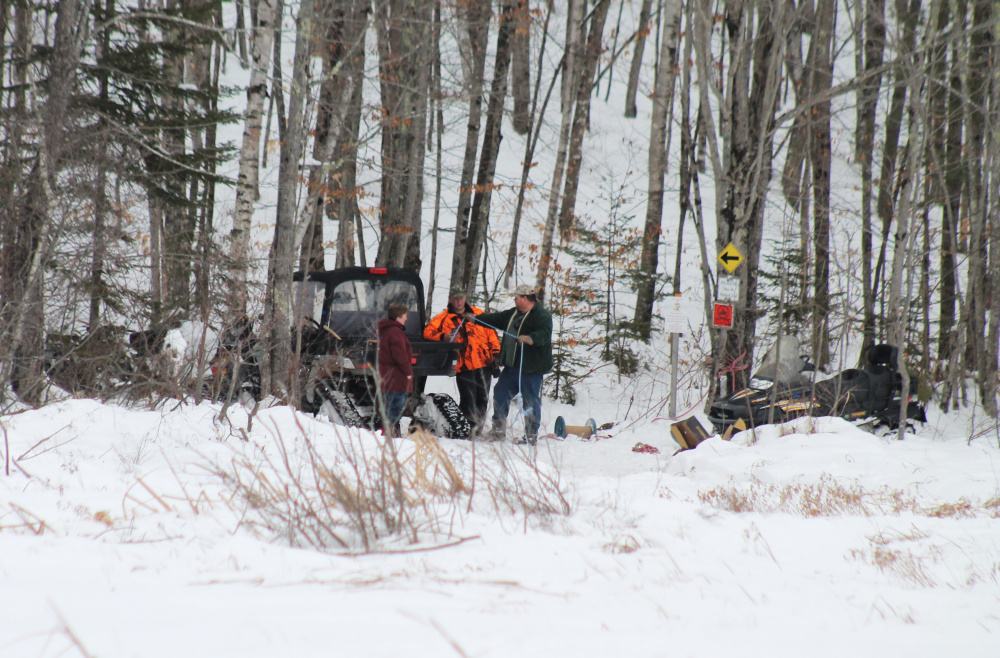 From left to right, Roberta Kemp, Max Kemp and Scott Kemp work to recover snowmobiles that got stuck in a bog in the Leeds/Wales area on Monday.