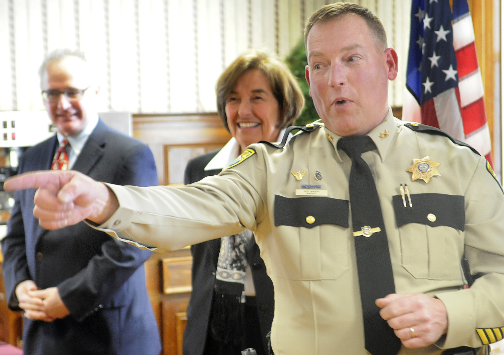 Ken Mason points to friends and relatives after being sworn in  Tuesday as the Sheriff of Kennebec County in Augusta.