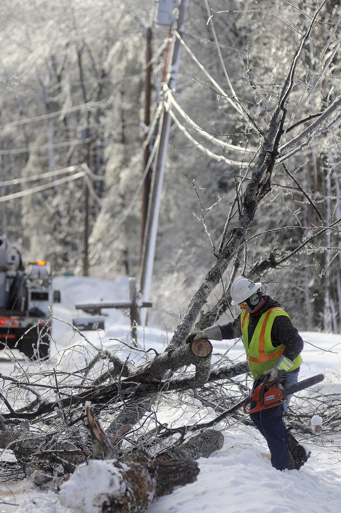 Central Maine Power Co. lineman Sam Pottle cuts a tree that fell on a power line Wednesday in Wayne.