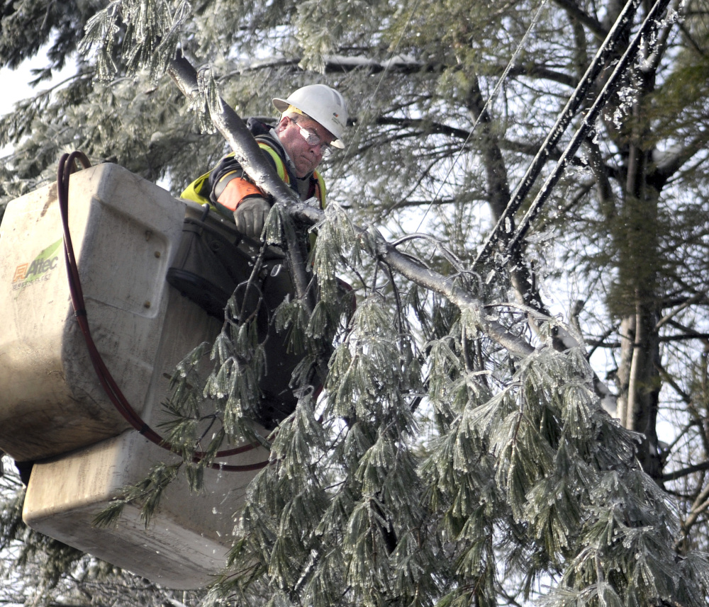 Central Maine Power Co. lineman Wayne Piper removes a limb from a power line Wednesday in Manchester.