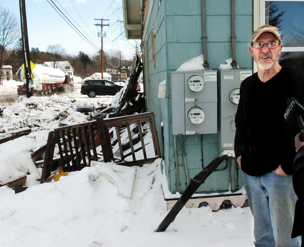 As a truck passes by Wednesday, homeowner Richard Faeth talks about the Tuesday evening truck accident that destroyed the porch in front of his home on Fairbanks Road in Farmington.