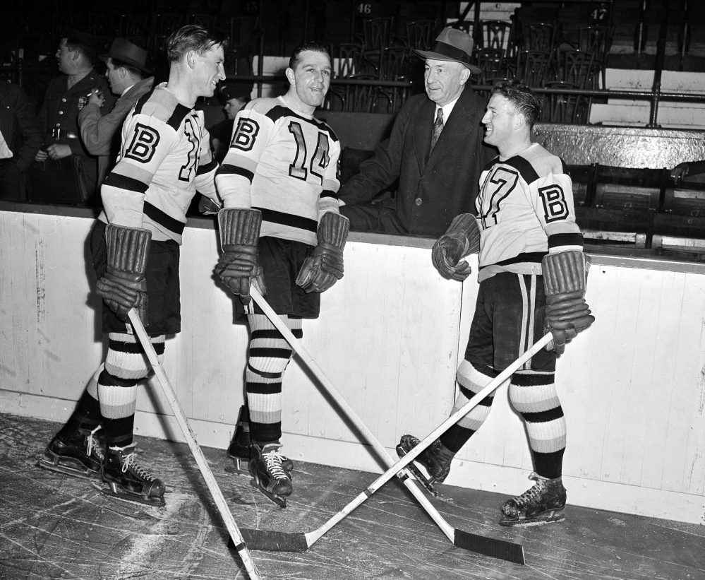 "In this October 1945 file photo, Boston Bruins manager ""Uncle Arthur"" Ross is pictured with his players, from left, Milt Schmidt, Porky Dumart and Bobby Bauer, known as the team's ""Kraut Line"", during hockey practice at Boston Garden in Boston. Schmidt, a hockey hall of famer, has died at the age of 98. Schmidt, the NHL MVP in 1951, was the league's oldest living former player."