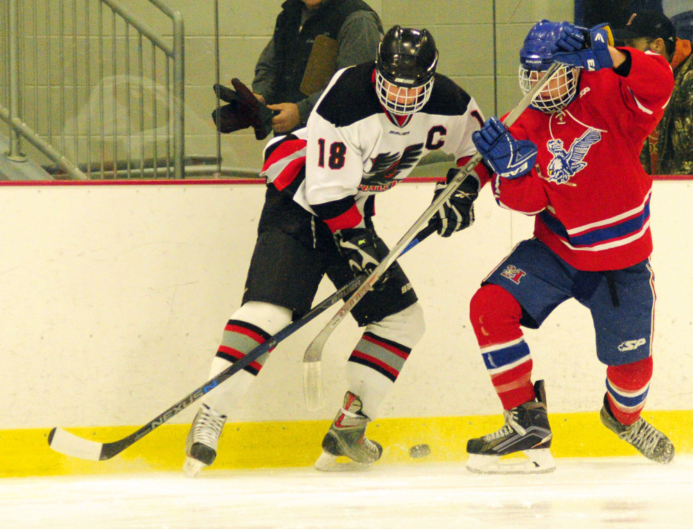 Maranacook/Winthrop's Matt Ingram, left, and Messalonskee's Tyler Lewis battle for a puck against the boards Wednesday at Bonnefond Ice Arena in Kents Hill.