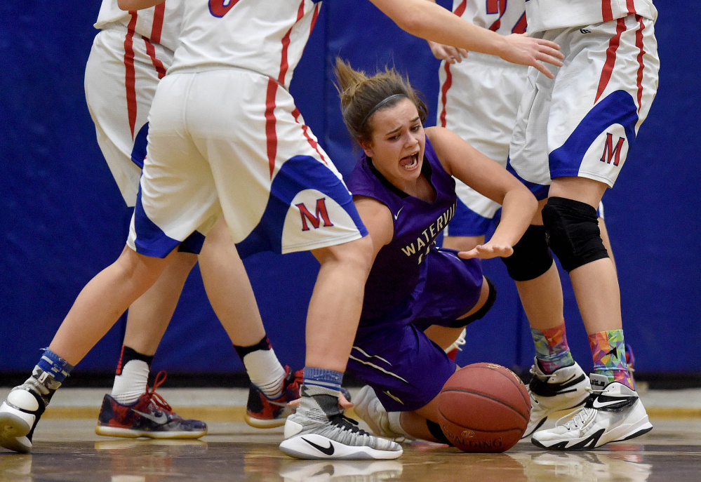 Waterville's Mackenzie St. Pierre falls to the court as she fights for the loose ball against Messalonskee on Wednesday in Oakland.