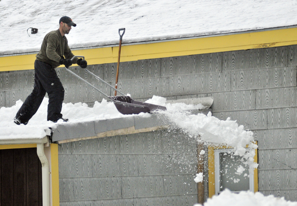 Michael Vachon shovels a roof Feb. 16, 2016, after an overnight snowstorm in Augusta. Vachon said he wanted to get weight off the building after a storm dumped several inches of snow, followed by freezing rain and rain.