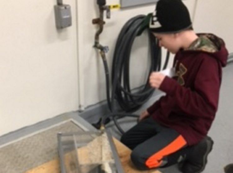 Forest Hills Consolidated School eighth grader Joey Poulin created a water filter during the Jackman Water District's open house. Parker Desjardins, also an eighth grader, not pictured, worked together with Poulin on their project.