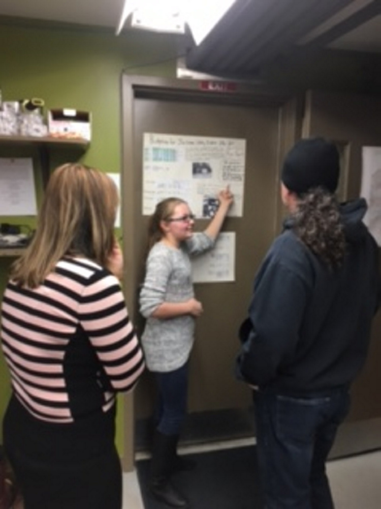Forest Hills Consolidated School eighth graders Sarah Hoyt, center, studied and reported on financial particulars during Jackman Water District's open house. Jacob Chagnot worked together with Hoyt on their project.